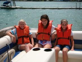 Young girls ride pontoon at Camp Friedenswald